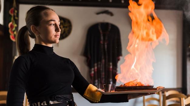 Camarero llevando plato con carne en fuego