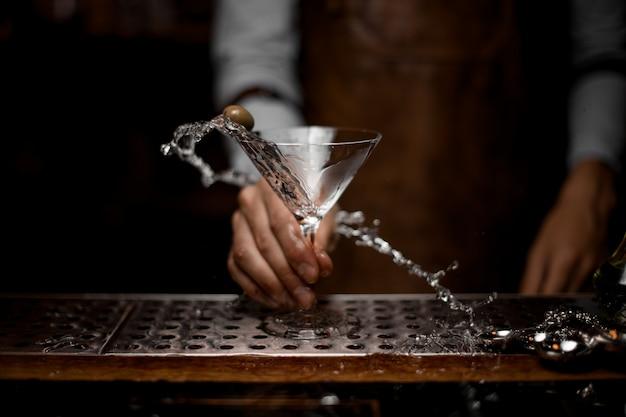 Camarero macho mezclando una bebida alcohólica transparente en la copa de martini con una aceituna
