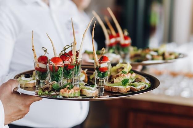 Un camarero mantiene una bandeja con bocadillos