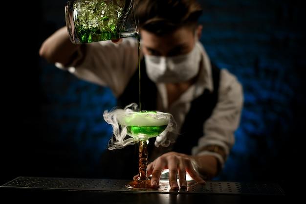 Camarero con máscara médica blanca vierte el cóctel en un vaso y míralo