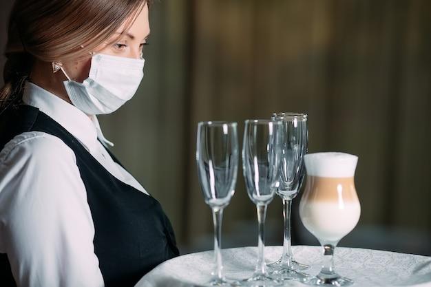 Camarero en una máscara médica sirve café con leche