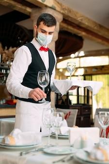 Un camarero con una máscara protectora médica sirve la mesa en el restaurante.