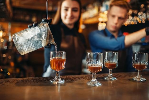 Camarero masculino y femenino en la barra del bar