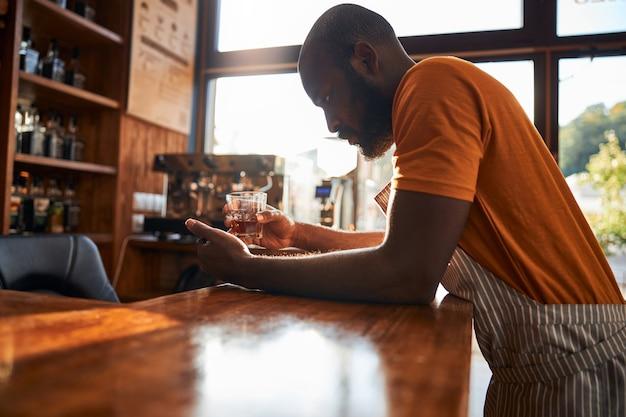 Camarero masculino guapo sosteniendo un vaso de whisky
