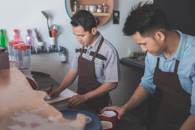 Camarero masculino preparando menú para clientes