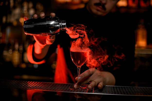 Camarero masculino vertiendo un humo en la copa de cóctel de la coctelera de acero