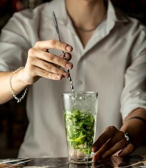 Camarero mezcla cóctel mojito con cuchara de metal