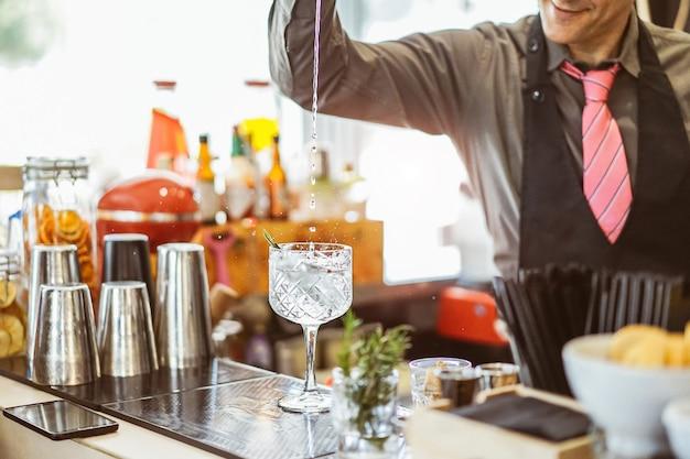 Camarero mezclando un cóctel en un vaso de cristal en un bar americano