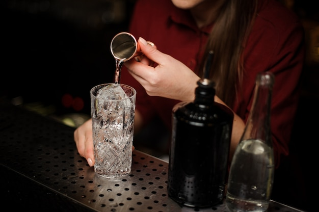 Camarero mujer vertiendo un poco de ginebra en una copa de cóctel