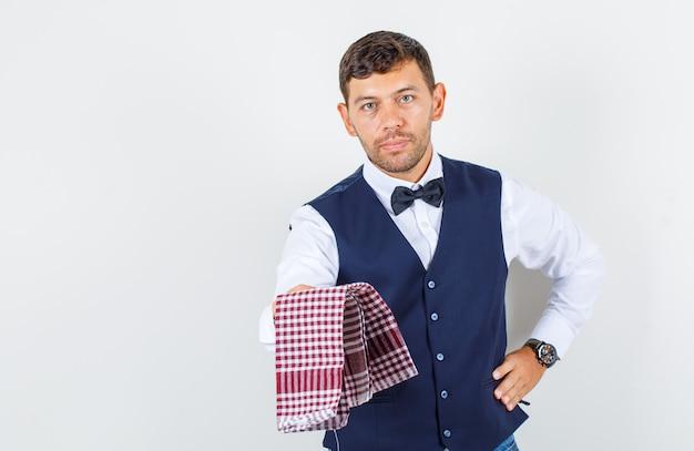 Camarero ofreciendo toalla a cuadros en camisa, chaleco, jeans y mirando serio, vista frontal.
