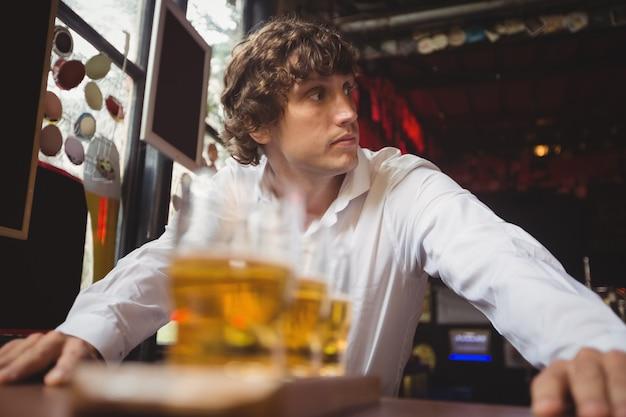 Camarero de pie cerca del mostrador con vasos de cerveza