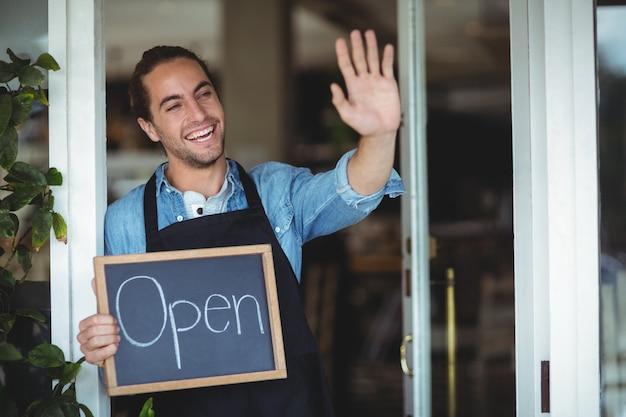 Camarero de pie en la puerta del café con pizarra con señal abierta