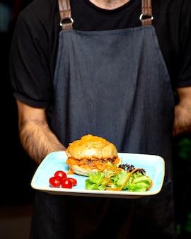 Camarero con plato de hamburguesa con ensalada verde