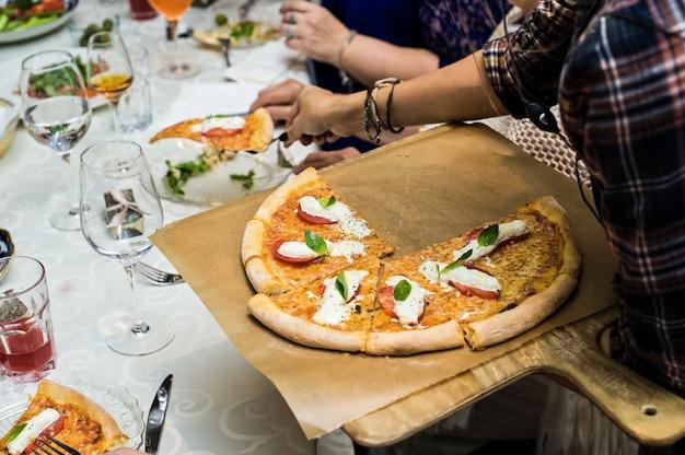 El camarero pone pizza en platos de invitados, servicio de restaurante.