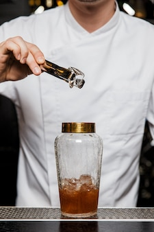 Camarero poniendo hielo en una coctelera de vidrio