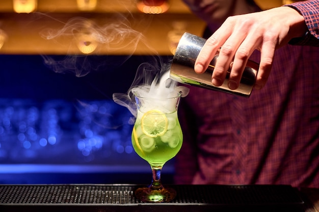 Camarero preparando un cóctel alcohólico verde con rodajas de limón y hielo.