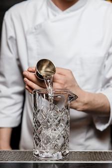 Camarero preparando un cóctel en el bar, agregando alcohol al vaso mezclador con un aparejo