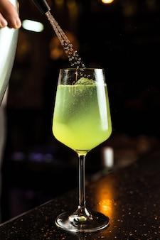 Camarero preparando un cóctel verde con hielo en una copa de vino, agregando agua de soda