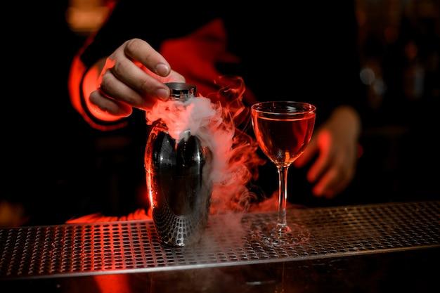 Camarero profesional con una tapa de la coctelera humeante cerca del cóctel en el vaso
