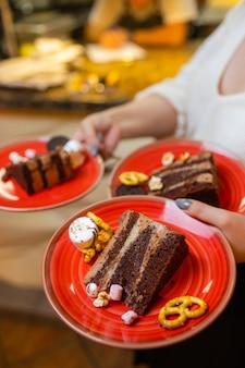 Un camarero que sirve dos trozos de pastel en platos. él sostiene dos platos con una mano.