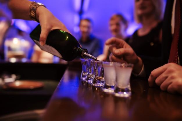 Camarero que vierte bebidas alcohólicas fuertes en vasos pequeños en el bar, tiros en una discoteca o bar