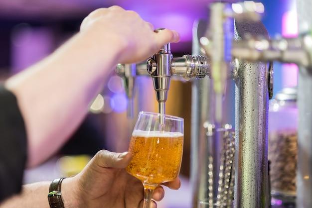Camarero que vierte la cerveza de cerveza dorada en un vidrio.