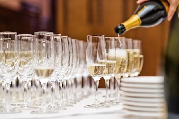 Camarero que vierte el champán en la copa de vino en restaurante.
