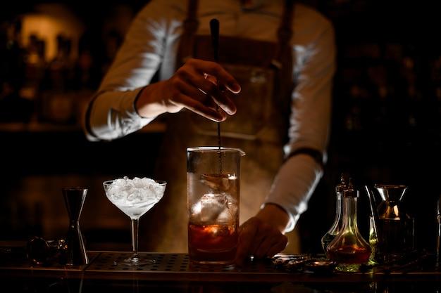 Camarero revolviendo un cóctel en la taza de vidrio de medición