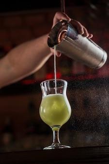 El camarero rocía sobre el vidrio iluminado con un cóctel frío verde brillante en la barra del bar y hace que el fuego llamee sobre él.