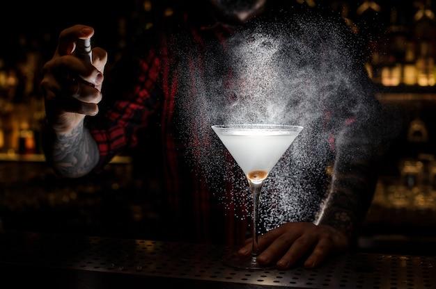 Camarero rociando amargo en el vaso con cóctel fresco