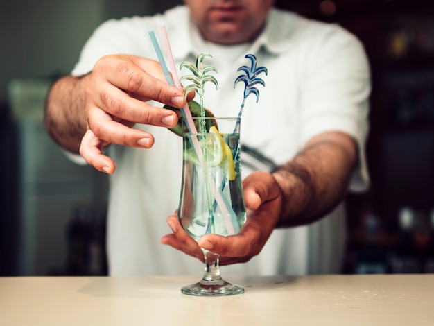 Camarero sin rostro que sirve vaso de bebida