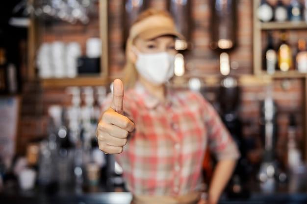 Camarero rubia con uniforme con máscara protectora facial muestra su pulgar hacia arriba con una mano mientras que la otra descansa sobre su cadera