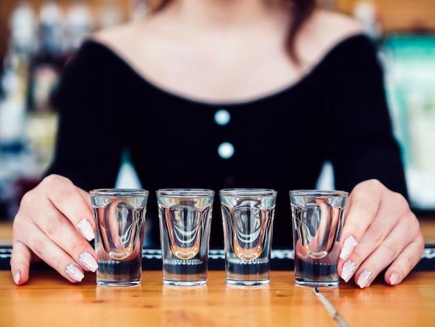 Camarero de sexo femenino con la fila de vasos de chupito