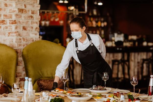 Camarero de sexo femenino joven en uniforme con máscara médica y guantes que sirven en el restaurante. copie el espacio.
