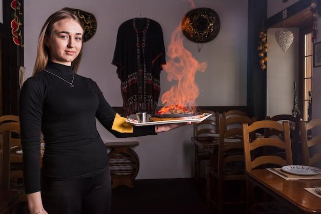 Camarero de sexo femenino que lleva la carne ardiente en restaurante