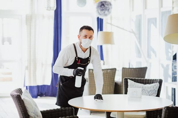 Camarero de sexo masculino en delantal negro, máscara médica y guantes que limpian la mesa blanca en el restaurante con una botella de desinfección.