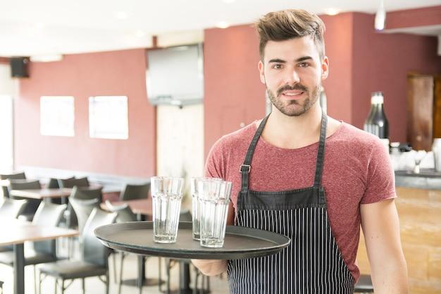 Camarero de sexo masculino que sostiene la bandeja con los vidrios vacíos en la barra