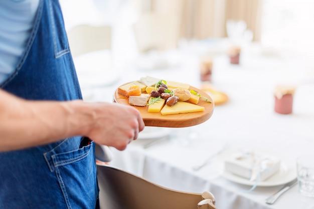 Camarero sirviendo aceitunas y queso sobre tabla de madera.