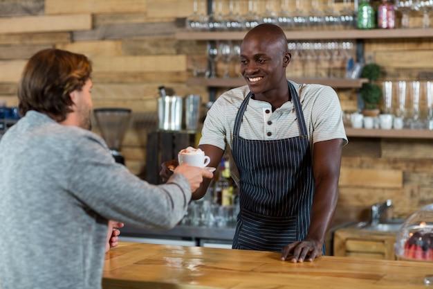 Camarero sirviendo café al cliente masculino