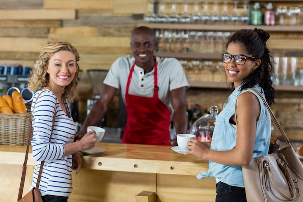 Camarero sirviendo café a clienta