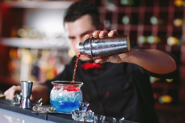 Camarero sirviendo cócteles frescos en un vaso elegante