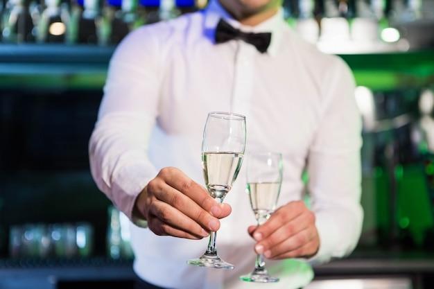 Camarero sirviendo una copa de champán en barra de bar en bar