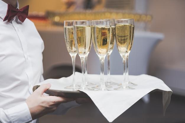 Camarero sirviendo copas de champán en una bandeja en un restaurante.