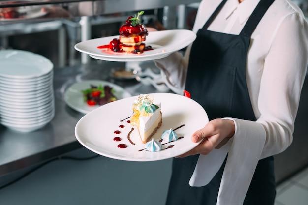 Camarero sirviendo en movimiento de servicio en el restaurante. el camarero lleva platos.