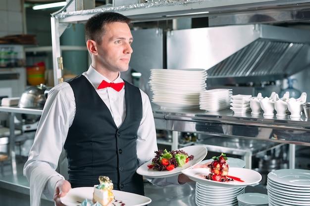 Camarero sirviendo en movimiento de servicio en el restaurante. el mesero lleva platos