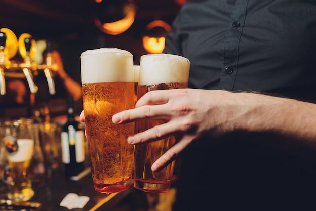 Camarero sirviendo vasos de cerveza fría en la bandeja