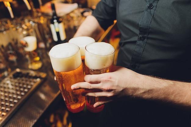Camarero sirviendo vasos de cerveza fría en la bandeja.