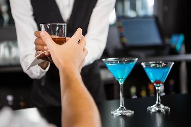 Camarero sirviendo whisky en barra de bar en bar