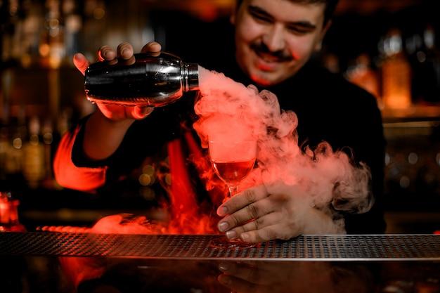 Camarero sonriente con bigotes vertiendo un humo en la copa de cóctel desde la coctelera