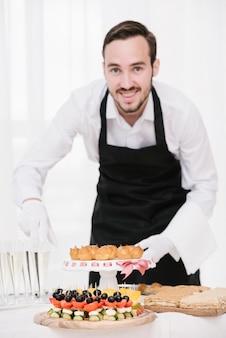 Camarero sonriente con comida y bebida en una mesa